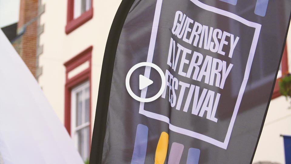 A Guernsey Literary Festival flag against a backdrop of the St.Peter Port high street