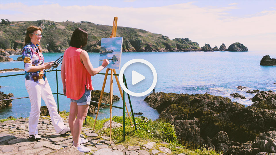 two women painting on a Guernsey shoreline