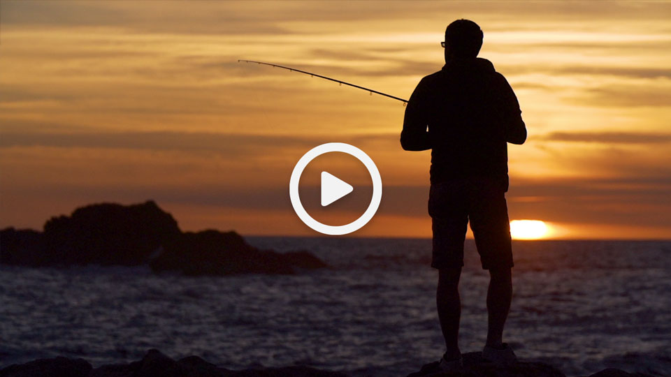 A man fishing at L'ancresse bay in Guernsey