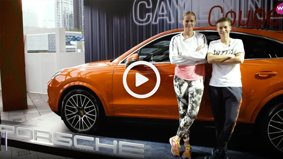 two professional tennis players stood next to an orange car